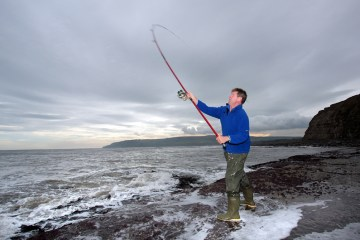 an angler casting with long rod on Yorkshire coast