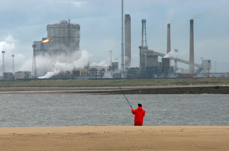 An angler fishing the Tees in front of factories