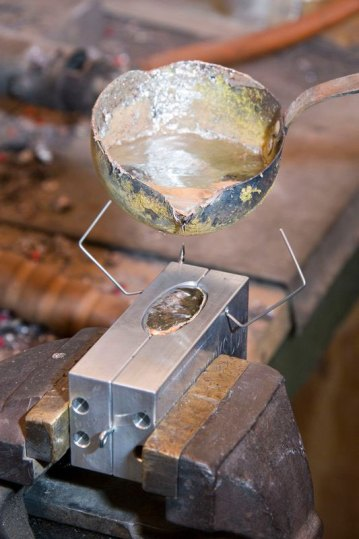 finishing pouring lead into a mould