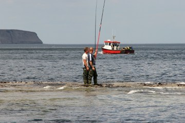 two anglers at Ravenscar with boat in background