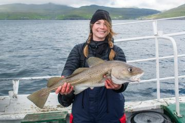 a smiling female Canadian visitor with a cod