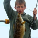 a young angler with a ballan wrasse
