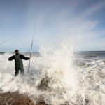 an angler on an exposed shoreline hit by wave