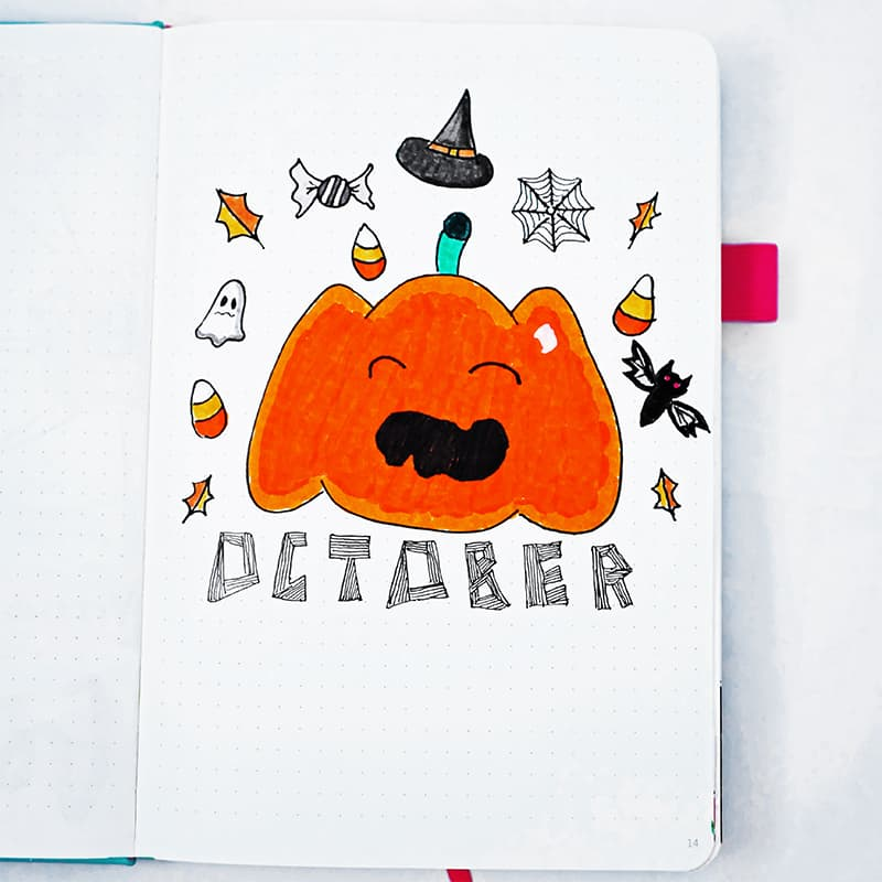 Bullet journal halloween theme cover page for October with candy corn and other halloween doodles