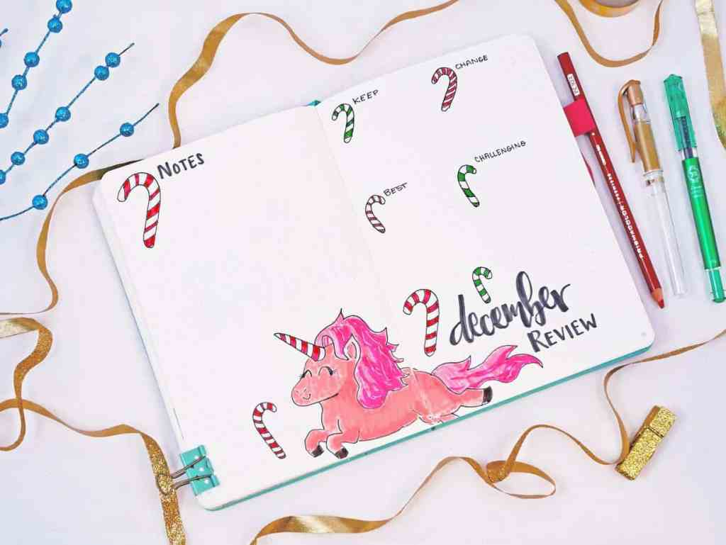 Bullet journal holiday theme monthly review with unicorn and candy cane doodles