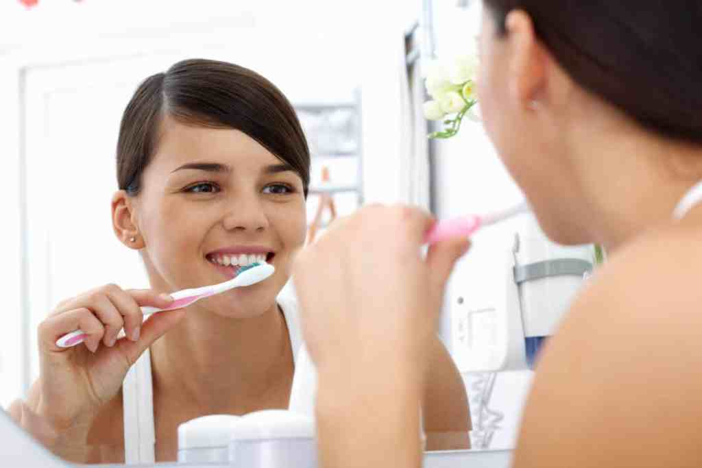 Woman happy brushing her teeth to destroy bacteria as part of her morning routine.
