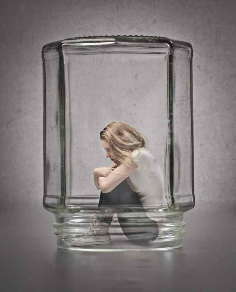 Woman isolating herself in literal glass jar.