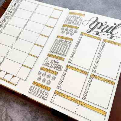 Yellow bullet journal weekly setup for April with pretty doodle trackers