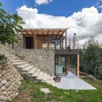 Diseño de moderna casa de campo, presenta exteriores en piedra con hermosa vista hacia la naturaleza