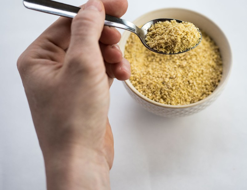 Vegan parmesan cheese in white bowl on white background. There is a white hand with a small spoon holding vegan parmesan cheese.