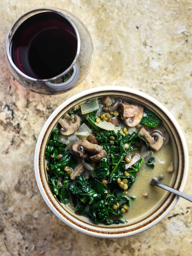Mushroom kale soup in a bowl with a glass of red wine.