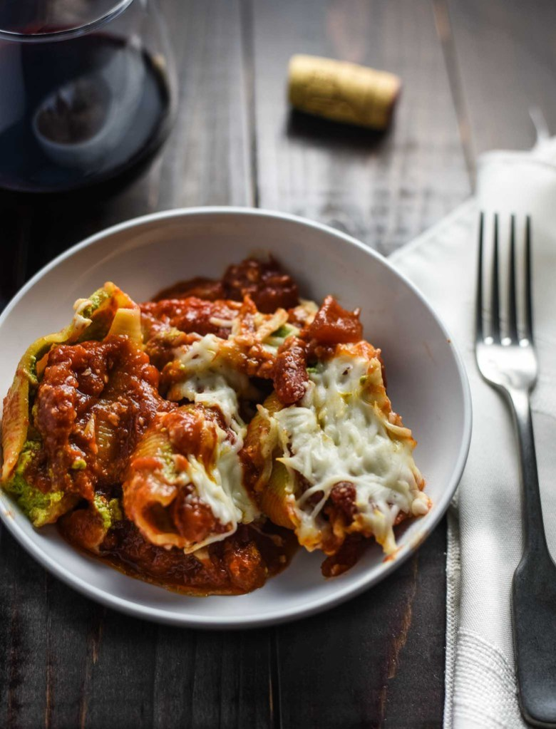 Vegan stuffed shells in a white pasta dish with a fork on a white napkin and a glass of red wine.
