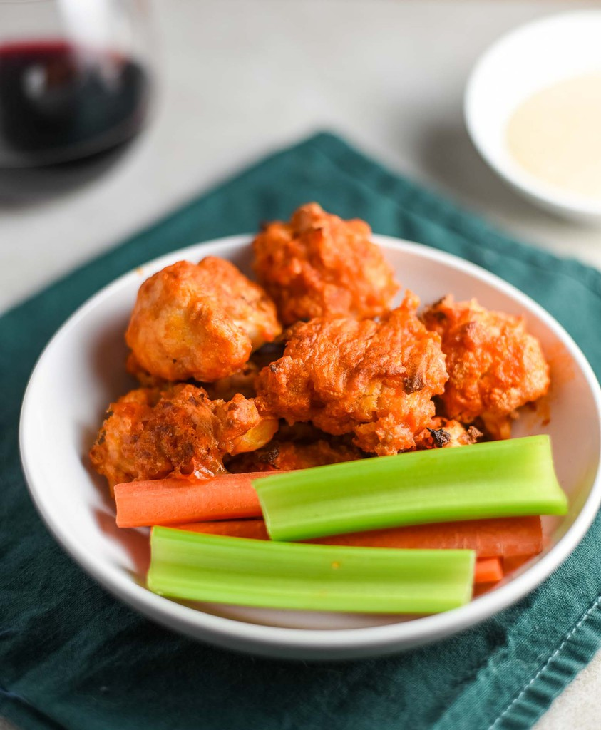 Cauliflower buffalo wings with carrot sticks and celery in a white bowl on top of a green napkin.