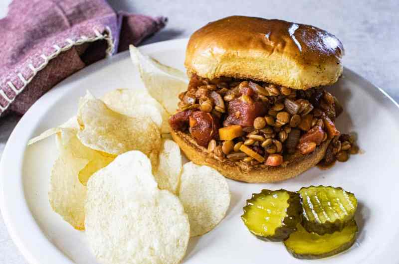 Lentil sloppy joes with potato chips and pickles on a white plate