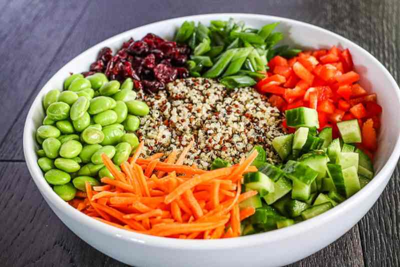 edamame, cranberries, green onions, red bell pepper, cucumber, carrots and quinoa layered in a white bowl.