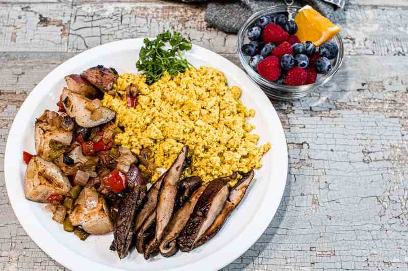 Crispy potatoes, scrambled tofu eggs and sliced portobello steaks on a white plate next to a small cup of fresh fruit.