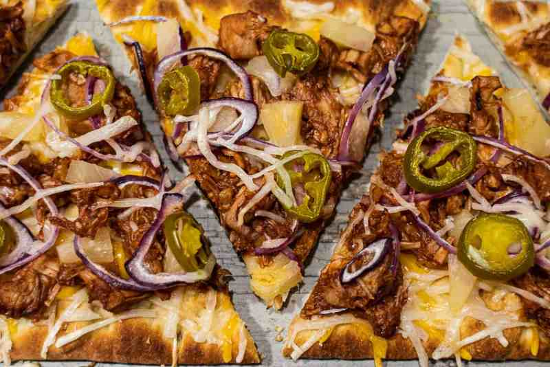 BBQ jackfruit pizza cut into triangles on a cutting board.