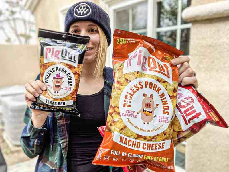 woman holding three bags of pigless pork rinds