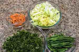 Prepped bowls of kale, cabbage, green beans and sliced carrots