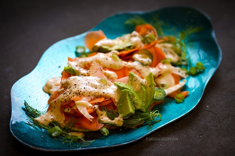 Tahini salad dressing drizzled over the carrots, avocado, and fennel.