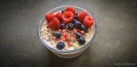 Layered overnight oatmeal with chia, topped with berries.