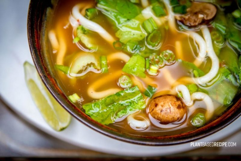 Spicy vegan udon noodle soup with vegetables.