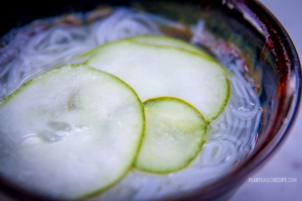Rice stick noodles and cucumbers in a vinegar broth.