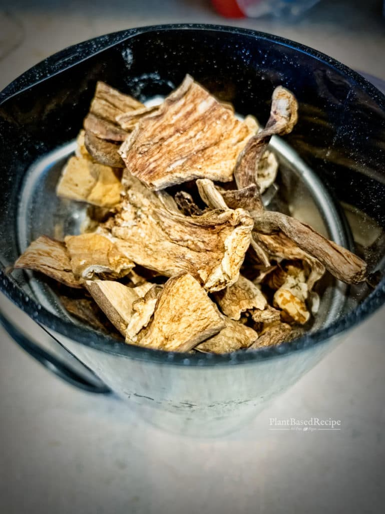 Dried mushrooms being ground to a powder using a coffee grinder