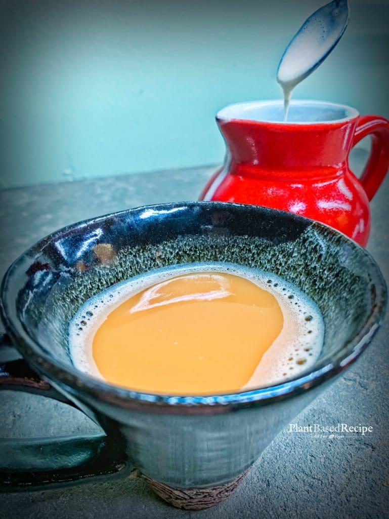 Oat milk added to hot tea.