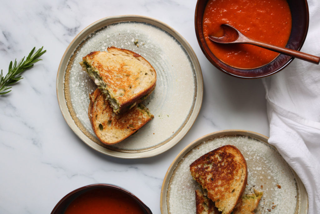 homemade vegan tomato soup in a pot next to vegan pesto grilled cheeze sandwiches on plates