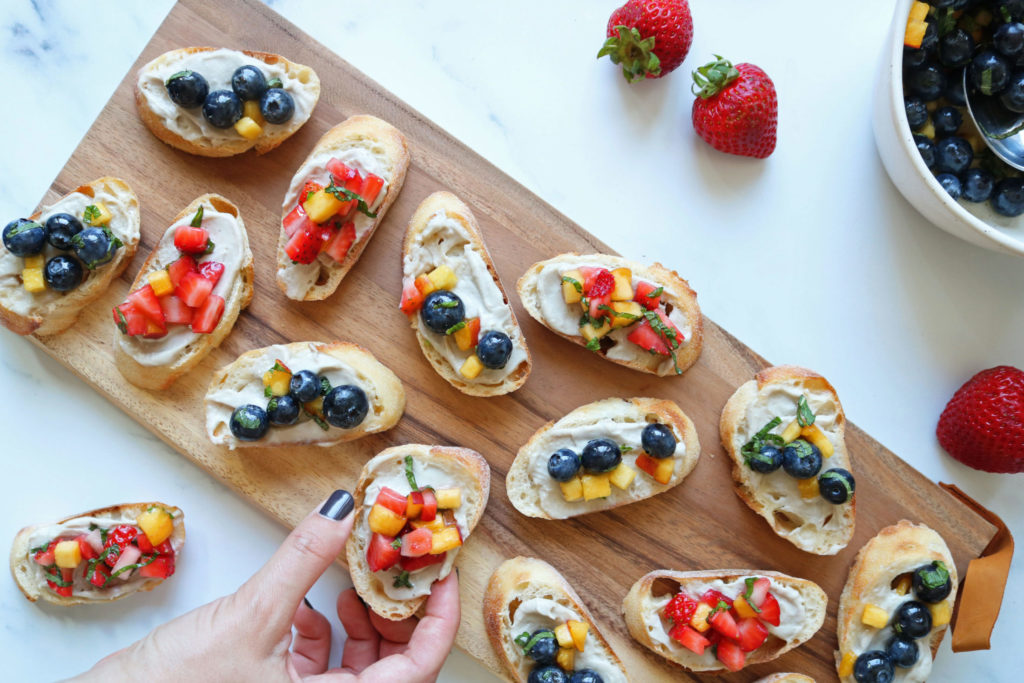 vegan fruit bruschetta piece covered in strawberry and blueberry on a wooden serving tray
