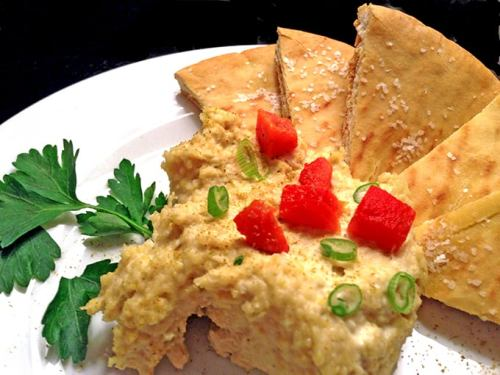 Dish of homemade hummus with toasted pita bread.