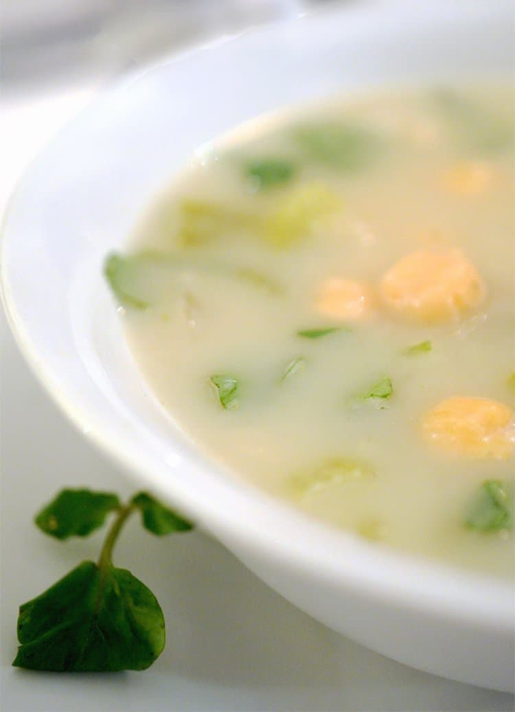 white bowl of fennel soup with watercresss and chickpeas as garnishes,