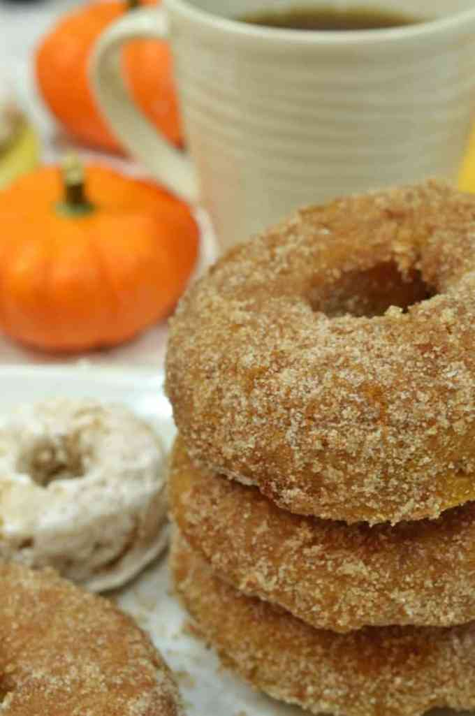 Pumpkin donuts, stacked in front of a cup of coffee with small pumpkins in the background.