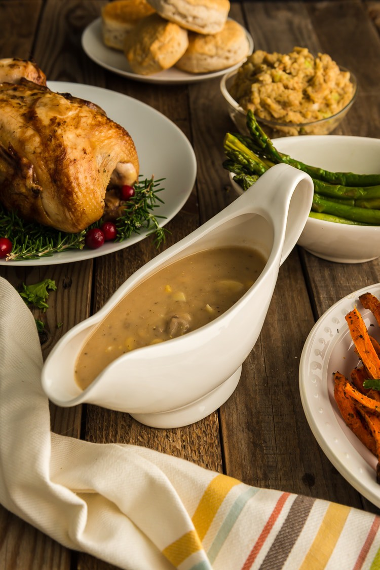 Thanksgiving table featuring turkey gible gravy, roast turkey, asparagus, and homemade dressing.