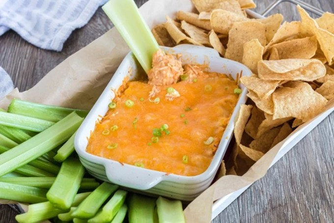 Easy Buffalo chicken dip with celery and tortilla chips.