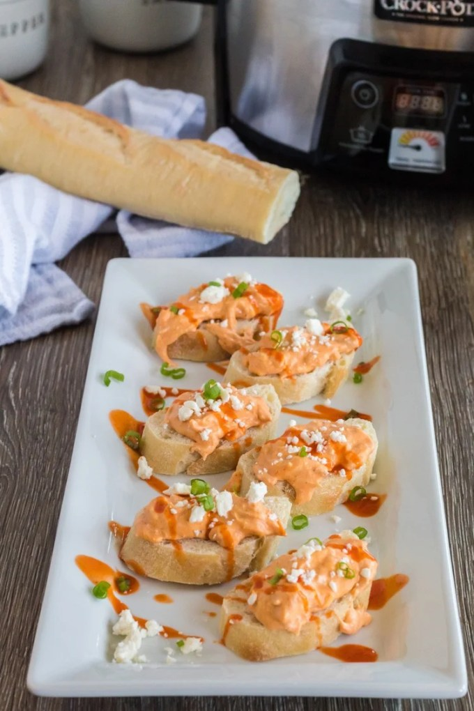 Buffalo wing dip spread over a plate of crostini.