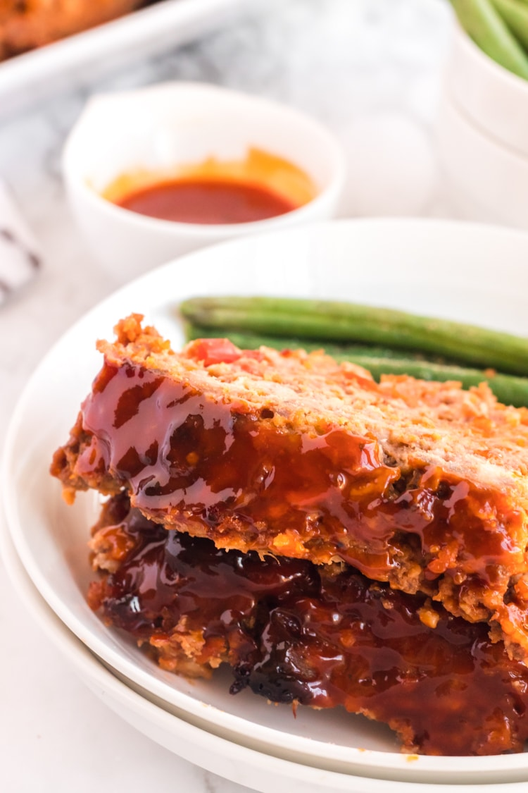 Serving plate with two slicres of meatloaf on it with green beans.