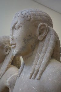 """Over half of surviving Ancient Greek kouros sculptures (from c. 615 – 485 BC) are found wearing dreadlocks. In Ancient Greece, kouros sculptures from the Archaic period depict men wearing dreadlocks while Spartan hoplites (generally described as fair-haired) wore formal locks as part of their battle dress."""