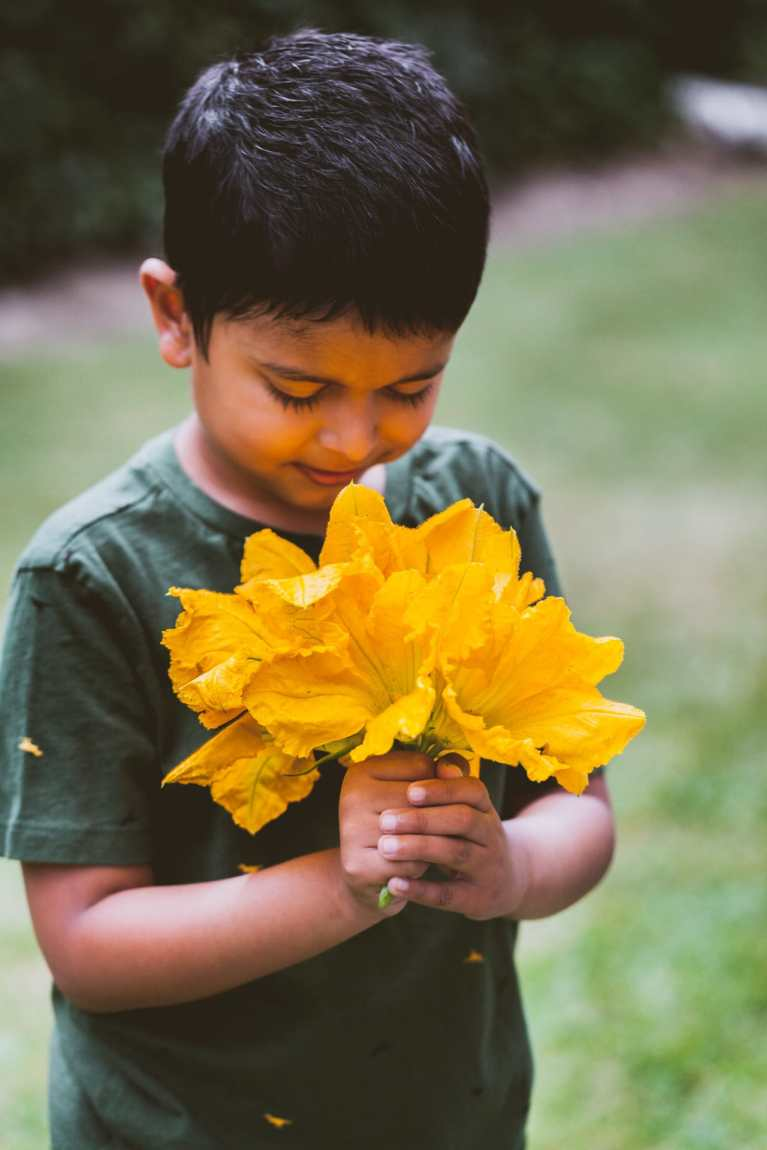 Avyan holding a bunch of fresh zucchini flowers