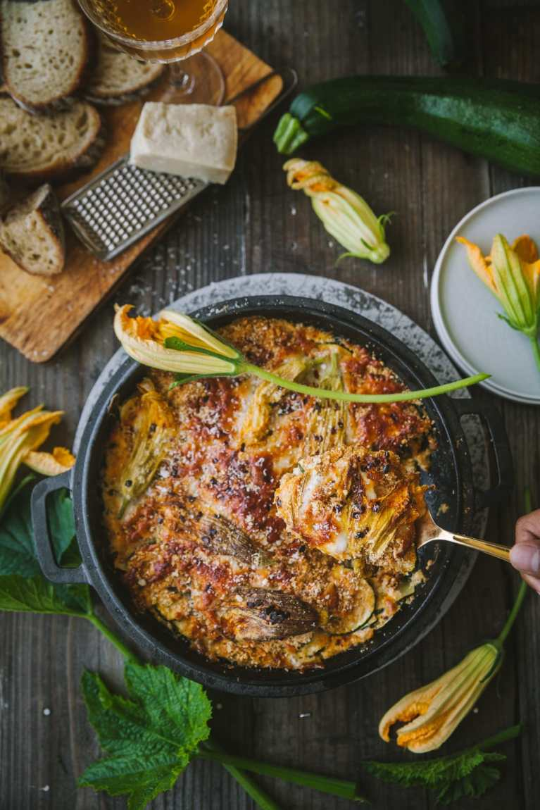 Zucchini gratin on a dish with cheese and zucchini blossoms every where