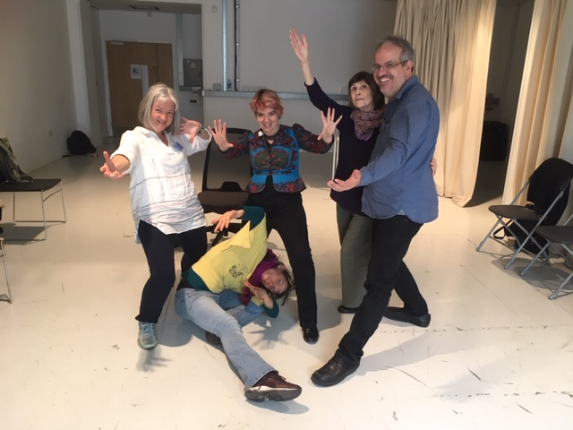 Five people in a tableaux showing various responses to the workshop: Four with open arms, many open palms and one person on the floor her head threaded through someone's leg.