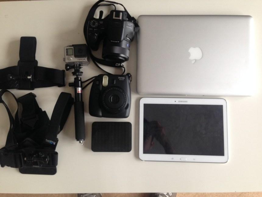 Photo d'un ordinateur, une gopro et un polaroid pour faire le tour du monde en voyage