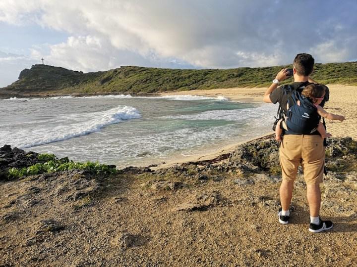 un homme prend une photo de la plage avec un bébé sur le dos
