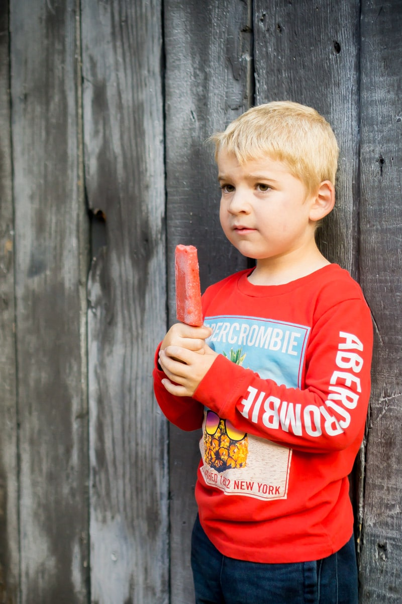 A kid with a popsicle after his first day of kindergarten