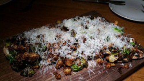 Grilled Flatbread with brussels sprouts, buttermilk, sheep's milk cheese and crispy pig ear
