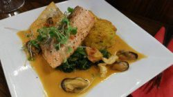 Charred salmon with mussels, lobster butter and risotto cake