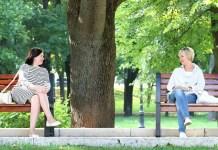 Mulheres sentadas em bancos separados