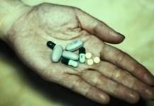Mão aberta com comprimidos