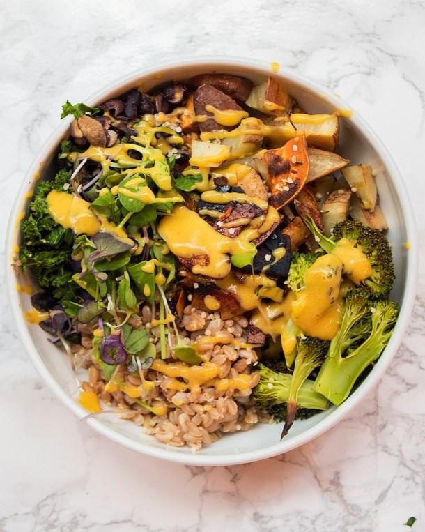 vegan farro sweet potato broccoli bowl with queso and coconut bacon